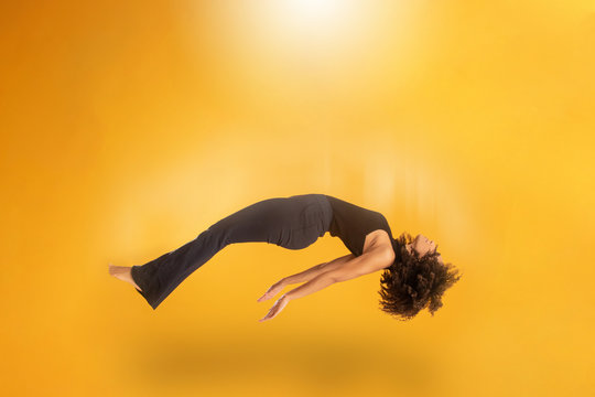 Side view of afro hair woman in zero gravity or being abducted by a UFO. Girl is flying or floating in the air. Side view of person. Over yellow background. Spiritism. Rising to the heaven.