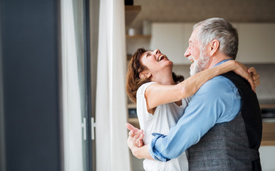 A senior couple indoors at home, laughing and hugging.