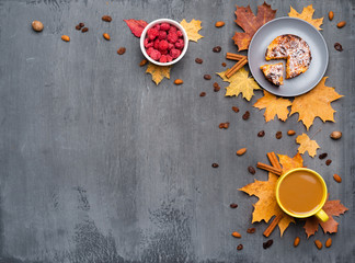 Wall Mural - Seasonal autumn background. Frame of colorful maple leaves and a cup of hot drink, coffee, latte or cappuccino, nutmeg, cake, raspberries and cinnamon over grey.