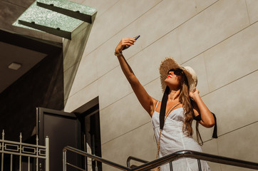 Beautiful slim girl in a white dress and a straw hat takes a selfie on the phone in the city in summer.