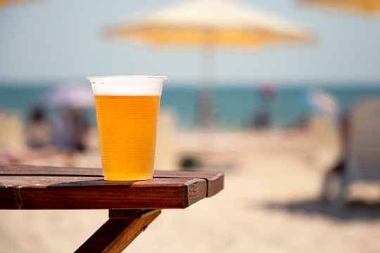 Wet glass of golden cool tasty beer on the wooden table on the shore of the sea or ocean on the sunset. Concept of beach bar or party. Alcohol beverage.