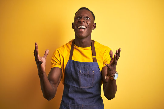 African american bartender man wearing apron standing over isolated yellow background crazy and mad shouting and yelling with aggressive expression and arms raised. Frustration concept.