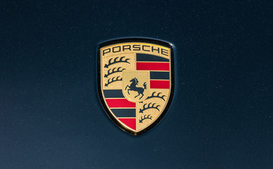 AACHEN, GERMANY MARCH, 2017: Porsche Sign Close Up on a black car. Ferdinand Porsche founded the company in 1931 with main offices in the centre of Stuttgart.