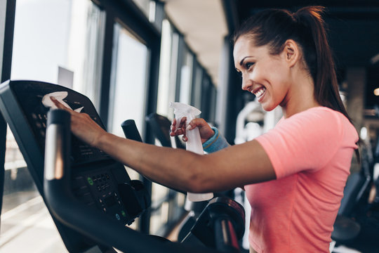 Young happy and smiling woman cleaning and weeping expensive fitness gym equipment with sprayer and cloth.