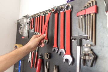 Man hand holding wrench. Other tools on the wall. Wall mural