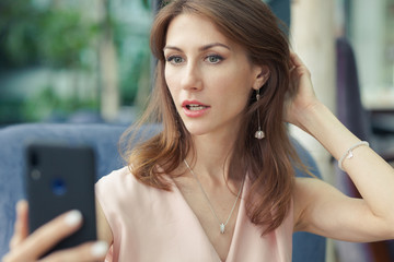 Portrait of a beautiful young brunette woman in a pink dress sitting in a blue armchair. girl holds a mobile phone in hand and takes a selfie.
