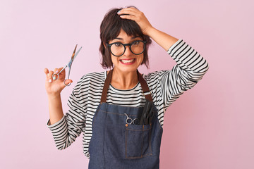 Hairdresser woman wearing apron and glasses holding scissors over isolated pink background stressed with hand on head, shocked with shame and surprise face, angry and frustrated. Fear and upset