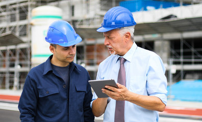 Fototapete - Two architect developers reviewing building plans at construction site using a tablet