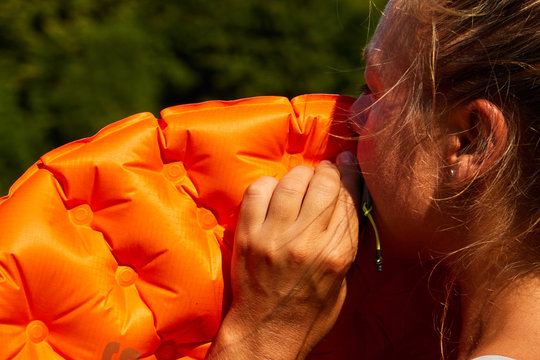 girl inflates sleeping mat in nature