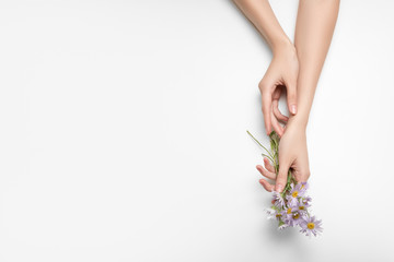 Beautiful manicured woman hands hold a bouquet of flowers. White background.