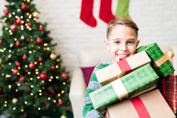 Boy Holding Christmas Gifts At Home