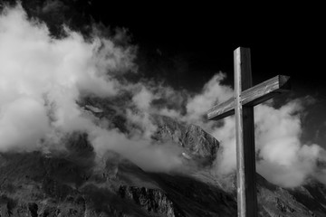 Close up  plain wooden summit cross (Jesus Christ crucifix) with the Alps mountain ranges, low hang thick clouds and dramatic dark black sky. Black and white image for Halloween or spiritual concept.