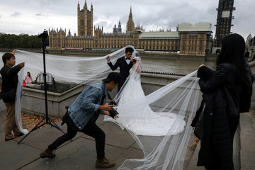 A bride and groom are photographed near the Houses of Parliament in London