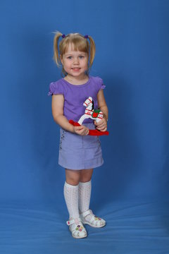 Little girl, with a wooden horse in her hands, on a blue background.