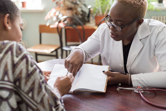 Hispanic patient signs treatment agreement with African female doctor. Young people of mixed race. The trust of the patient and the doctor. Voluntary Informed Consent