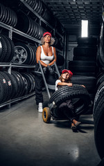 Strong female worker and her little helper have fun while looking for right tyres at warehouse.