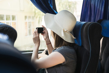 Young woman tourist in hat sits on a bus and takes a selfie on the phone.