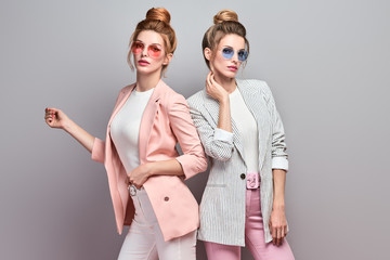Wall Mural - Two Beautiful fashionable woman sisters in Trendy autumn outfit, stylish hair, makeup. Slim friends in jacket, skinny on grey fall background. Adorable girl, stylish fashion autumnal look