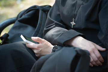 Unrecognizable nun in a black robe with a cross on his neck uses a smartphone
