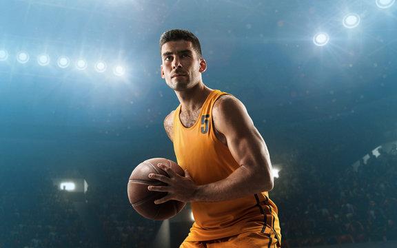 Professional basketball player on floodlit basketball arena with the ball