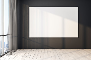 Blank poster on black wall in modern empty room with big windows and wooden floor, mock up.