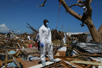 Personnel from the Royal Bahamas Police Force and a U.S. urban search and rescue team work to remove bodies recovered in a destroyed neighbourhood in the wake of Hurricane Dorian in Marsh Harbour