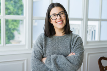 Young beautiful woman wearing glasses smiling cheerful standing casual at home on a sunny day