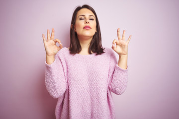 Young beautiful brunette woman wearing a sweater over pink isolated background relax and smiling with eyes closed doing meditation gesture with fingers. Yoga concept.