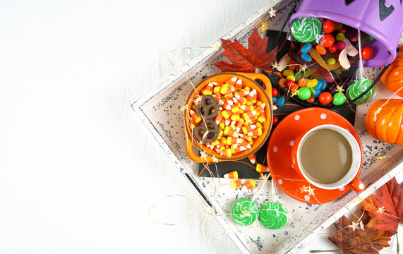 Halloween concept of relaxing with coffee and a tray of candy and treats, flat lay overhead with copy space.