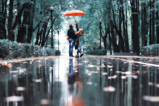 rain in the autumn park / young 25 years old couple man and woman walk under an umbrella in wet rainy weather, walk October lovers