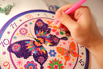 hand holds the stylus and glues the mosaic. diamond mosaic. set for gluing rhinestones on a butterfly picture. A lesson for the development of fine motor skills for children and adults.