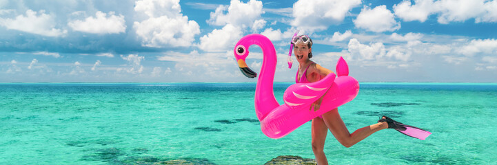 Wall Mural - Happy fun beach vacation woman tourist ready to jump in ocean swimming with snorkel fins and pink flamingo toy pool float. Goofy swimmer girl running on holidays panoramic banner.