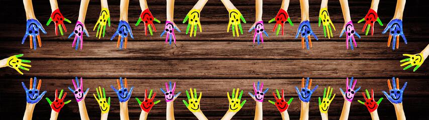 Bunt bemalte Kinderhände - Panorama - Hintergrund braunes Holz Holztextur