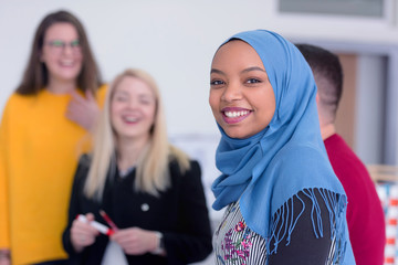 Female professor explain architectural projects to multietchnic students. Beautiful female muslim african american architecture student looking and smiling into camera. Wall mural