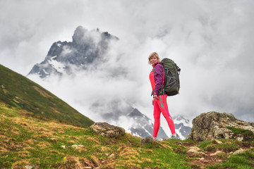 image of hiker with a backpack at the beautiful mountains background.