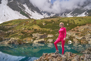 Hiking woman in red jacket stay at beautiful turquoise lake in mountains.