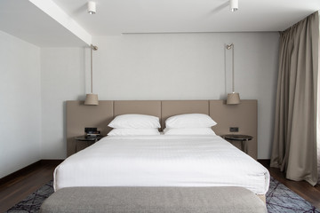 Interior of the modern bedroom in loft flat in light color style of expensive apartments