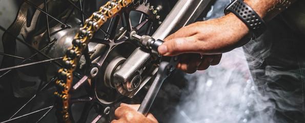 Fotobehang - Mechanic working on motorcycle in garage. Repair service.