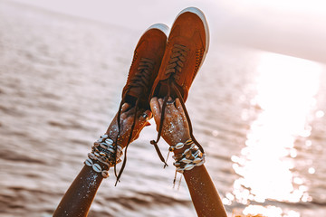 close up of woman hand holding shoes on the beach at sunset