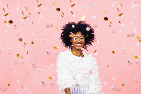 Happy woman with a big smile and confetti falling, on pink background