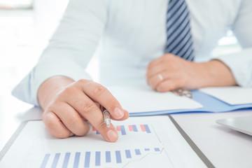 Businessman analyzes signing financial statements