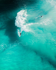 Aerial shot of surfers at sunrise on a nice blue ocean