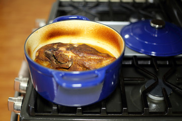 Braised pork roast cooked in a Dutch oven resting on the stove top.