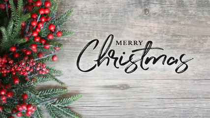 Wall Mural - Merry Christmas Text with Holiday Evergreen Branches and Berries Over Rustic Wooden Background