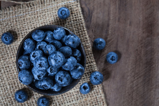 Blueberries in a brown ceramic bowl placed on sack and wooden table, taken on top view
