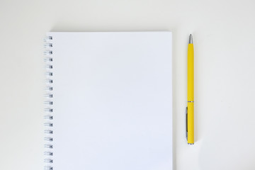 Mock up open notepad with spiral binder and yellow pen on white background, top view. Minimalism. Concept education