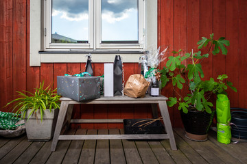 Outdoor front view of a gift present table bench with plants on a porch against red wooden plank wall and a window.