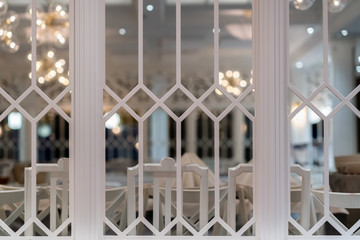 Beautiful large white decorative vintage indoor dining room window with table setting in the background.
