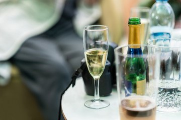 Candid snapshot of champagne glass and bottles on a small table. Traveler with camera taking a break resting with refreshments.