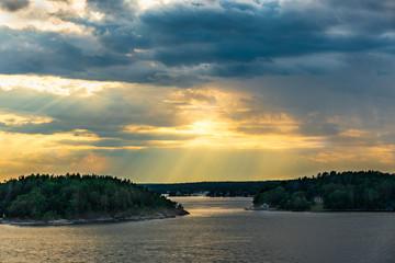 Beautiful summer Scandinavian midnight sun. Dramatic cloud sunset over islands and sea in the Swedish archipelago.